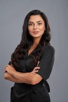 Adorabile cosmetologo con pelle chiara che indossa l'uniforme medica nera in posa all'interno. isolato su sfondo grigio studio.