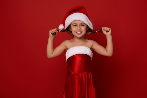 Adorabile bambina carina in abiti da babbo natale posa tenendo le trecce, sorride con un allegro sorriso a trentadue denti guardando la telecamera, posa su sfondo rosso con spazio copia per annuncio di natale e capodanno