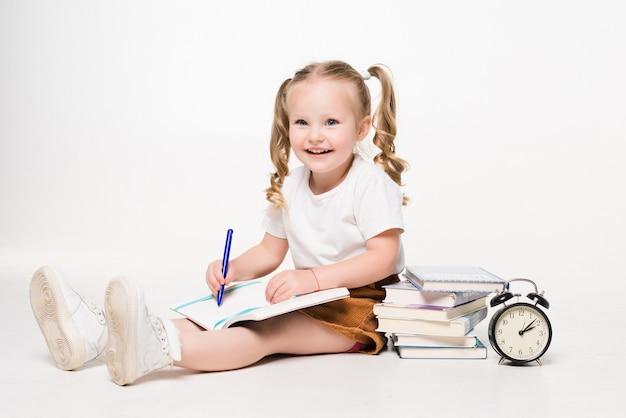 Adorabile bambina carina scrittura disegno in taccuino seduto sul pavimento isolato
