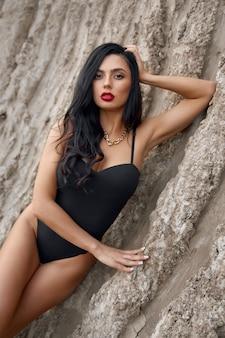 Adorabile donna dai capelli scuri vestita in lingerie sexy in posa sensuale sulla sabbia asciutta. modello di moda con trucco luminoso e capelli mossi scuri in piedi all'aperto.