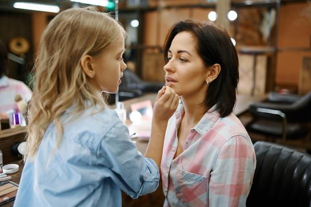 La figlia adorabile dipinge le labbra a sua madre in salone