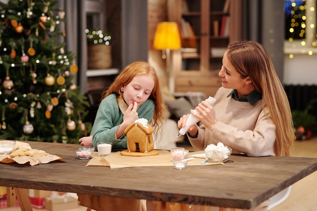Adorabile figlia che assaggia la panna montata dal tetto della casa di marzapane fatta in casa mentre sua madre la decora durante la conversazione
