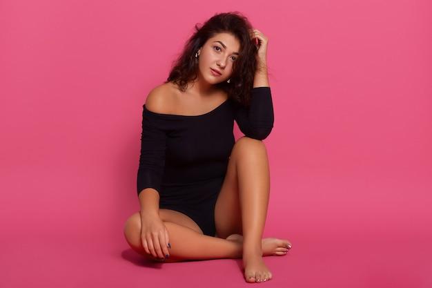 Adorabile donna sensuale elegante in tuta nera seduta sul pavimento, tiene una mano sul ginocchio e tocca la testa con un'altra, guarda la telecamera con sguardo calmo.