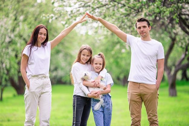 Famiglia adorabile nel giardino di fioritura della ciliegia il bello giorno di molla