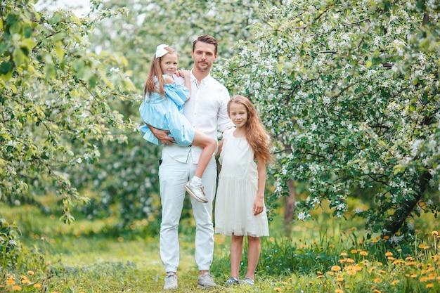 Adorabile famiglia nel giardino di ciliegio in fiore in una bella giornata di primavera