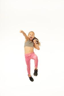 Adorabile bambina che fa posizione di combattimento e urla mentre salta in studio. isolato su sfondo bianco