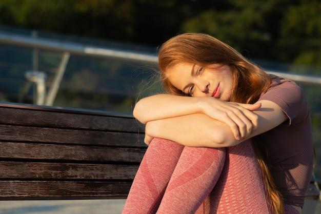 Adorabile fitness giovane donna con i capelli rossi che riposa dopo l'allenamento. spazio per il testo
