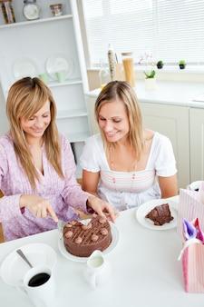 Adorabile amico che taglia una torta al cioccolato per un compleanno seduto in cucina