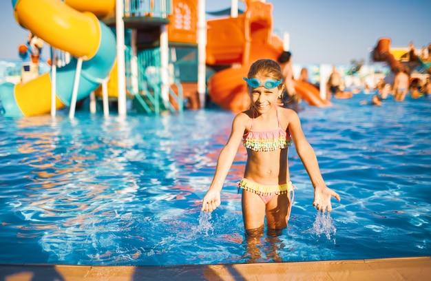 Un'adorabile ragazza con gli occhiali blu per nuotare e un costume da bagno luminoso si trova in una piscina con acqua limpida vicino al lato e schizza mentre alza le mani
