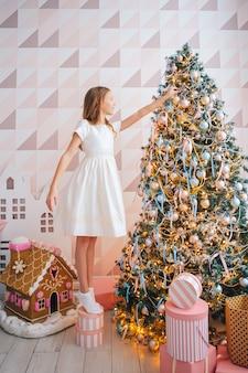 La ragazza adorabile decora l'albero di natale al chiuso. buone vacanze di natale