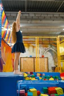Adorabile ragazza che salta sul trampolino per bambini