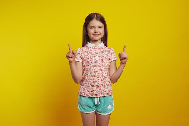 Adorabile bambina mostra promo con punti gioia sopra con entrambi gli indici