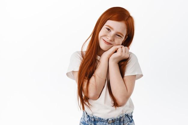 Adorabile ragazza con i capelli rossi e le lentiggini, si appoggia sulle sue piccole mani e sorridi carina, esprimi amore e cura, ammira qualcosa, in piedi sognante contro il muro bianco