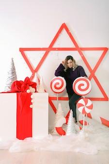 Adorabile ragazza seduta su una grande scatola regalo bianca vicino a decorazioni natalizie rosse, caramelle e stelle. signora sorridente vicino all'albero di natale bianco