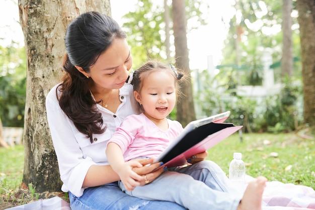 Animazioni di sorveglianza della ragazza adorabile con la madre all'aperto