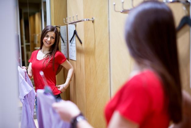 Un'adorabile ragazza felice sta provando cose nuove dal negozio stando davanti a uno specchio.