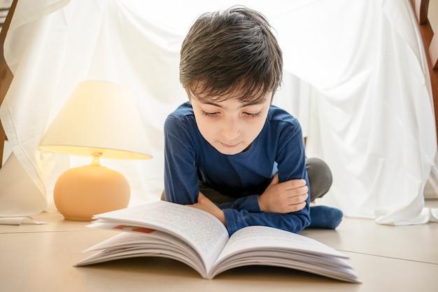 Adorabile bambino caucasico italiano che legge un libro e si trova in tenda a casa
