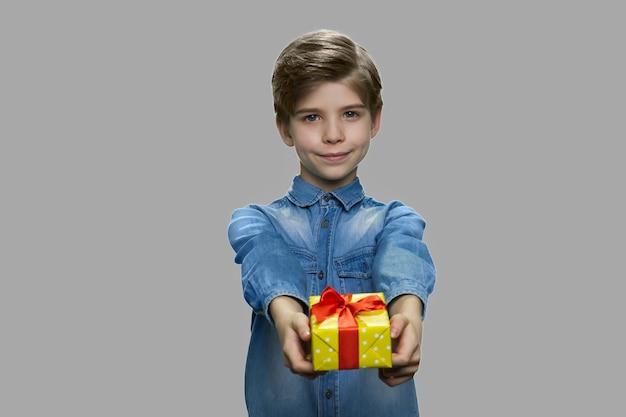 Adorabile bambino che dà confezione regalo alla telecamera. ragazzo sorridente del bambino che offre la casella attuale che sta contro il fondo grigio.