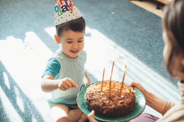 Il bambino adorabile indossa un cappello da festa mentre la madre gli sta dando una torta di compleanno