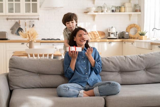 Adorabile figlio bambino che saluta la mamma con il compleanno della festa della mamma con una confezione regalo che chiude gli occhi della mamma eccitata