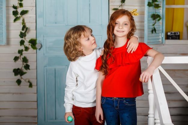 Bambini adorabili in vestiti colorati che godono della vacanza. momenti divertenti. concetto di vacanze di primavera. ragazzo e donna giocano.