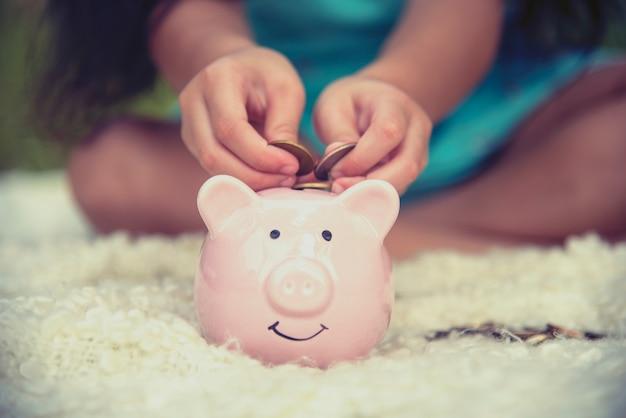 Mani adorabili dei bambini che risparmiano le monete in porcellino salvadanaio. felice investimento piccolo risparmio di denaro per il futuro della felicità.