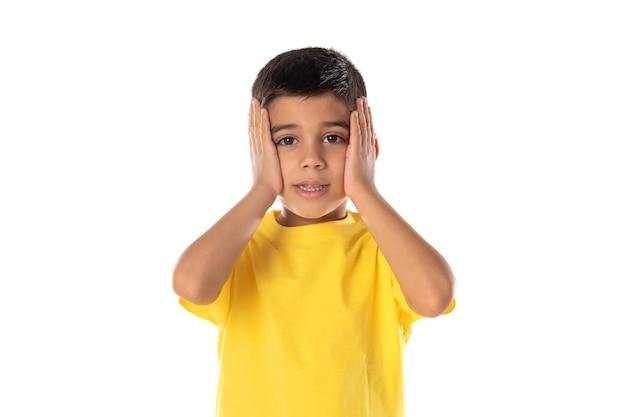 Adorabile ragazzo latino che indossa una maglietta gialla isolata su uno sfondo bianco