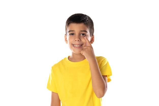 Adorabile ragazzo latino che indossa una maglietta gialla che guarda qualcosa di isolato su uno sfondo bianco