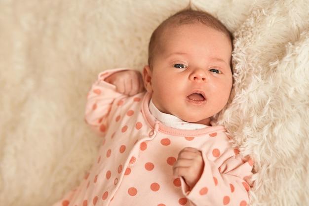 Adorabile bambino sdraiato sul letto, carina bambina al coperto, neonato che indossa il dormiente con pois, bambino che guarda la telecamera, tiene la bocca aperta, neonato con espressione rilassata studia il mondo intorno.