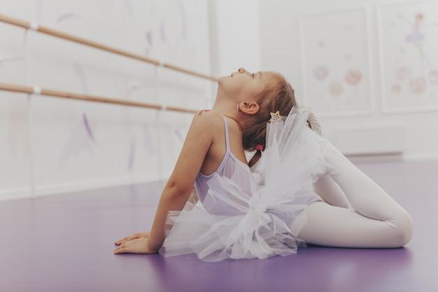 Piccola ballerina adorabile che si esercita alla scuola di balletto.
