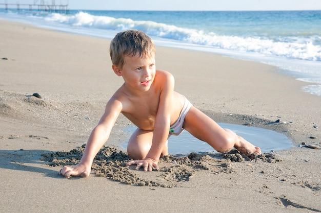 Adorabile ragazzino biondo che si diverte sulla spiaggia.