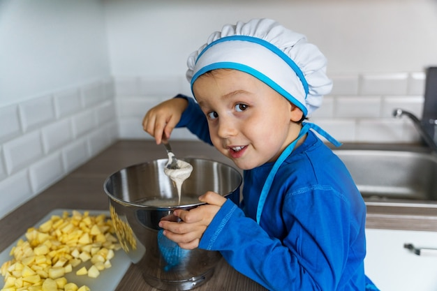 Adorabile ragazzino aiutando e cuocendo la torta di mele nella cucina di casa, al coperto