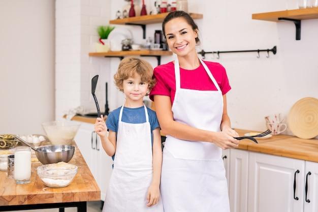 Ragazzino adorabile e sua madre in grembiuli bianchi che tengono stoviglie mentre cucinano insieme in cucina