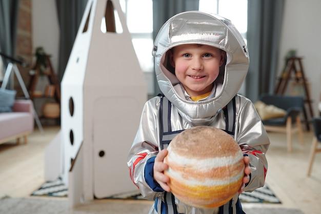 Adorabile ragazzino in tuta spaziale che tiene il pianeta del sistema solare