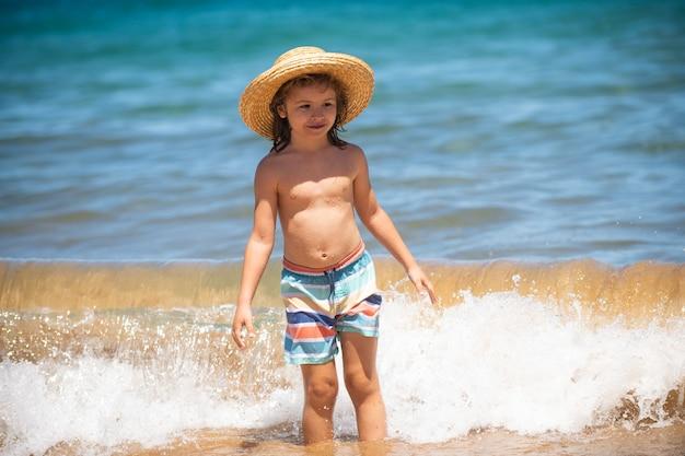 Adorabile ragazzino con cappello di paglia in spiaggia durante le vacanze estive ritratto di bambino giocoso sul mare...