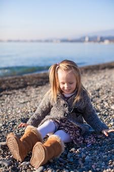 Adorabile bambina sulla spiaggia divertendosi al caldo giorno d'inverno