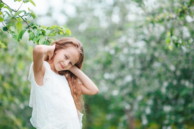 Bambina adorabile nel giardino fiorito della mela sulla bella giornata di primavera