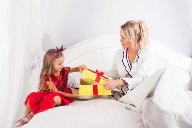 Adorabile bambina in abito luminoso e corona giocattolo sulla testa che apre la confezione regalo mentre è seduta con la madre sul letto, donna che augura buon compleanno alla figlia, saluto bambino in vacanza mattina, congratulazioni