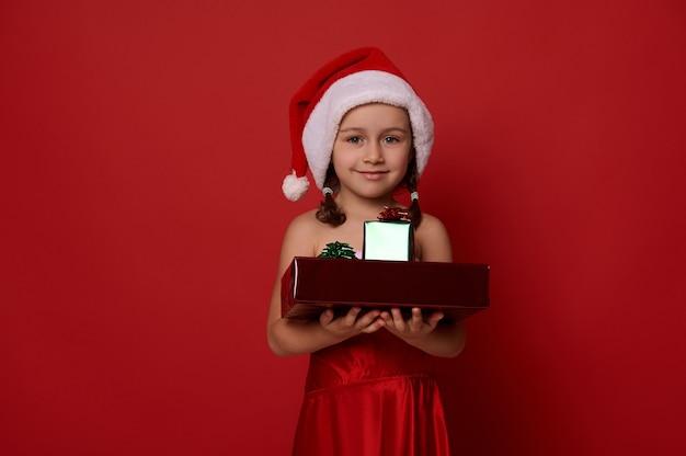 Adorabile bambina vestita in costume di carnevale di babbo natale, con doni sulle mani, sorride guardando la telecamera, posando su sfondo rosso. buon natale e anno nuovo concetto con copia spazio per ad