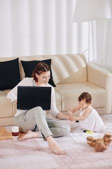 Bambina adorabile che dà la penna a sua madre che è seduta sul pavimento in soggiorno e lavora al computer portatile e riempie i documenti