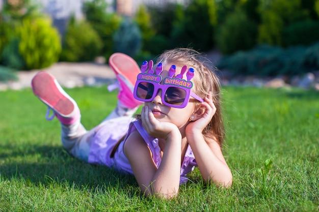Bambina adorabile nel sorridere di vetro di buon compleanno all'aperto