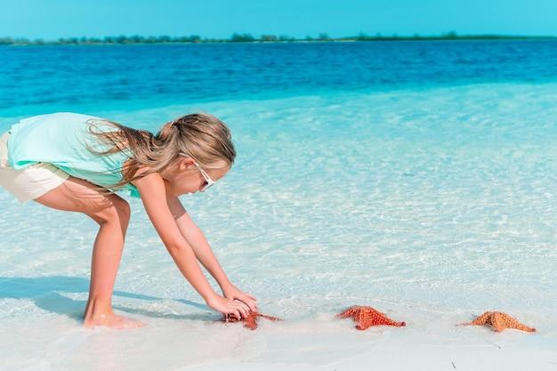 La bambina adorabile si diverte alla spiaggia tropicale durante le vacanze