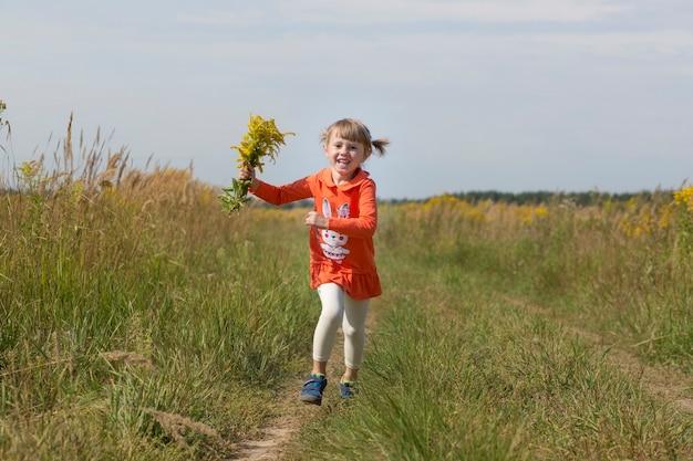 Bambina adorabile che tiene un mazzo dei fiori di campo gialli nel campo di autunno.