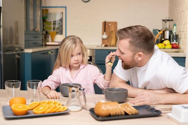 Bambina adorabile che tiene un cucchiaio con i fiocchi di mais dalla bocca del padre mentre entrambi seduti a tavola in cucina e fare colazione