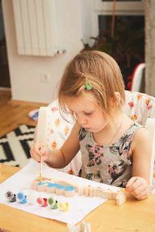 Adorabile bambina che dipinge nella stanza
