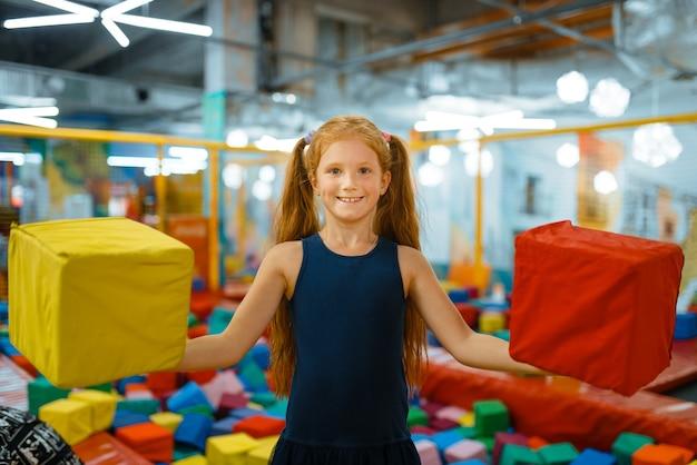 Adorabile bambina che gioca con i cubi morbidi, parco giochi nel centro di intrattenimento.
