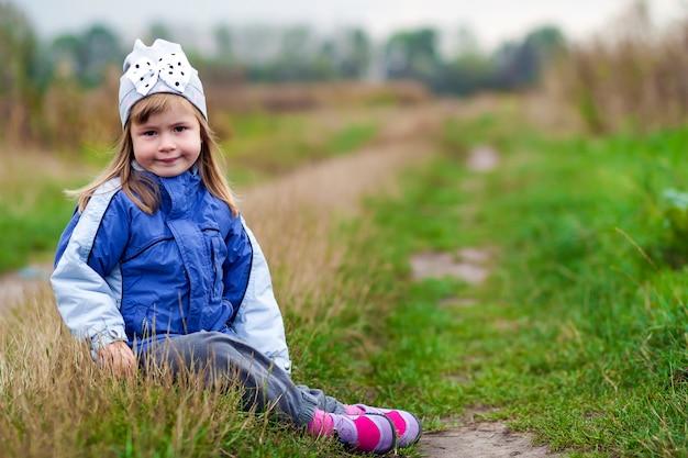 Bambina adorabile che posa sul fondo vago e che sorride dentro ad una macchina fotografica. indossa un cappotto e un cappello invernali. ragazza adorabile in autunno all'aperto.