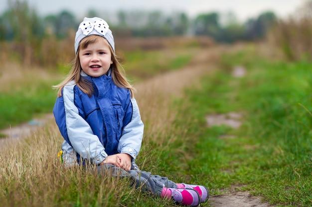 Bambina adorabile che posa su vago e che sorride dentro ad una macchina fotografica. indossa un cappotto e un cappello invernali. ragazza adorabile in autunno all'aperto.