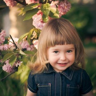 Adorabile ritratto di bambina in giardino, fiore di sakura