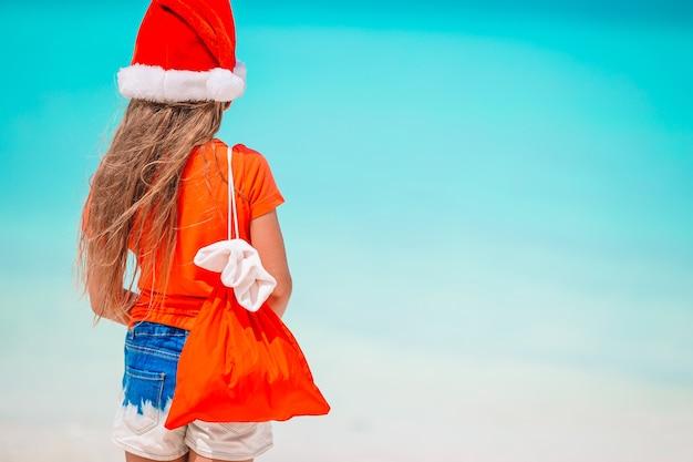 Bambina adorabile in cappello della santa con un sacco di regali sulla spiaggia tropicale
